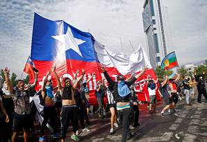 Manifestantes seguram bandeira chilena em Santiago no sexto dia consecutivo de violência nas ruas Foto: PABLO VERA / AFP