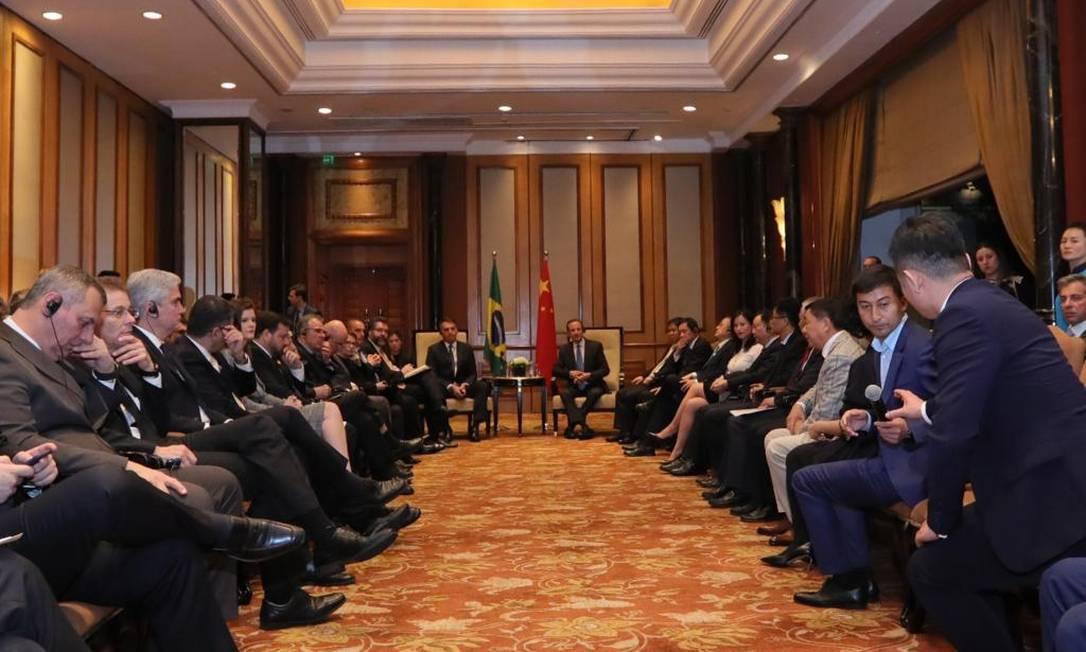 O presidente Jair Bolsonaro e o presidente da Fiesp, Paulo Skarf (ambos ao fundo) em encontro com empresários em Pequim Foto: Divulgação/Fiesp