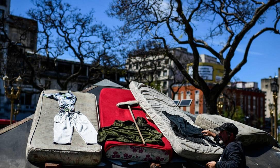 Um sem teto e seus pertences numa praça em Buenos Aires. Foto: RONALDO SCHEMIDT / AFP