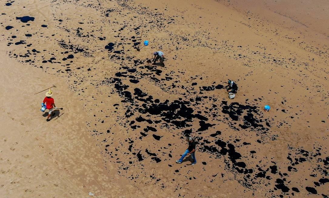 Voluntários removem resíduos de óleo na praia de Jauá, na cidade de Camaçari, Bahia. Origem do material permanece um mistério para pesquisadores e autoridades Foto: Mateus Morbeck / AFP - 17/10/2019