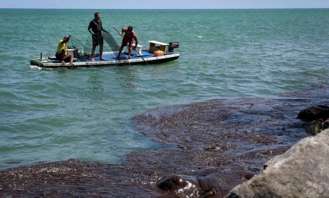 Pescadores ajudam a remover o petróleo derramado na praia de Janga, em Paulista, Pernambuco Foto: Leo Malafaia / AFP - 23/10/2019