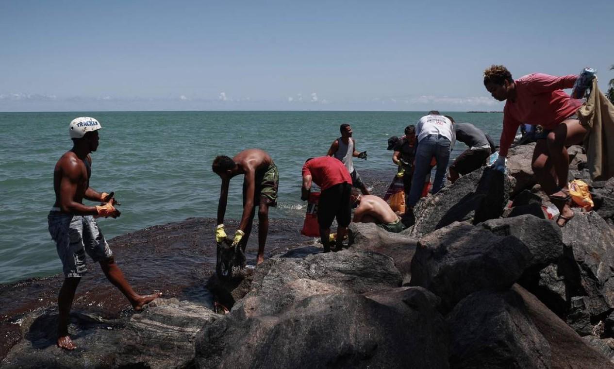 Voluntários trabalham na remoção de pretróleo da praia de Janga Foto: Leo Malafaia / AFP - 23/10/2019