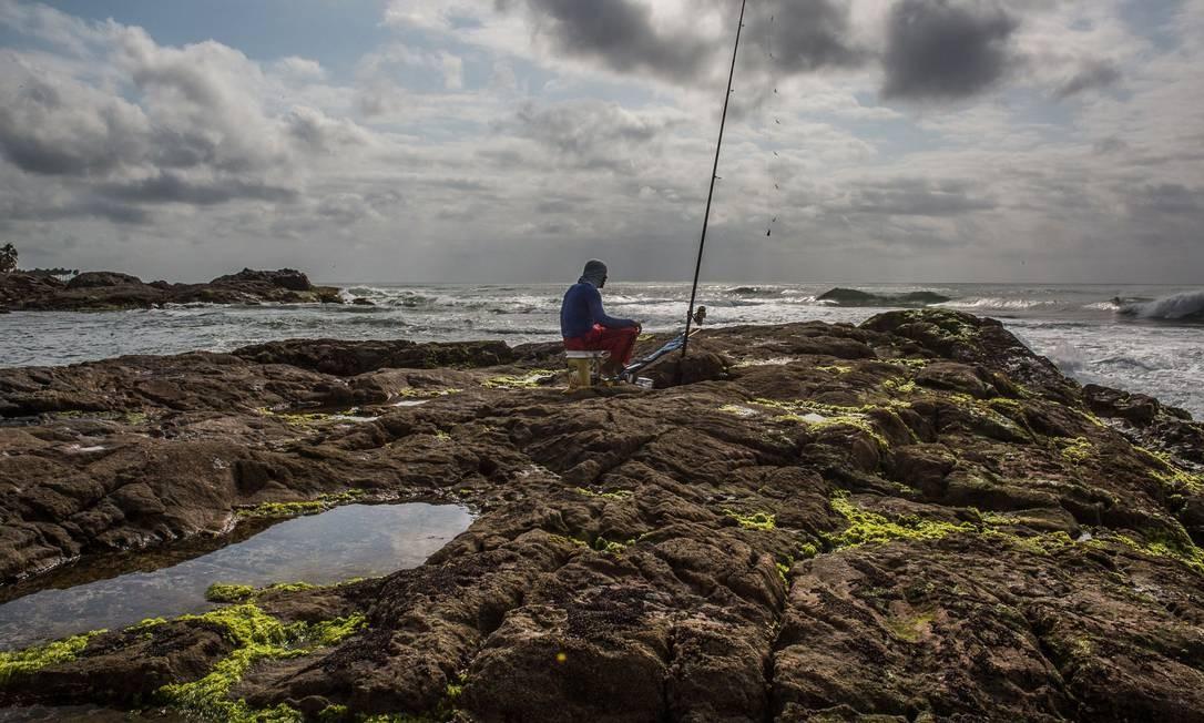Um pescador é visto em uma rocha coberta de petróleo na praia de Pedra do Sal, em Salvador, Bahia Foto: Antonello Veneri / AFP - 23/10/2019
