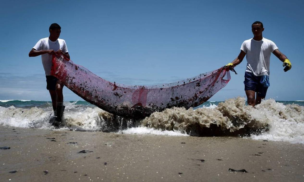 Voluntários removem resíduos de óleo na praia do Paiva, na cidade de Cabo de Santo Agostinho, Pernambuco Foto: Leo Malafaia / AFP - 21/10/2019