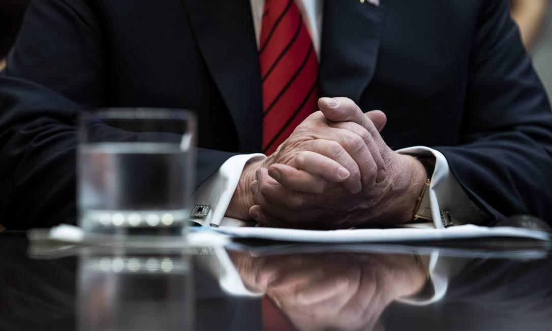 As mãos do presidente dos EUA, Donald Trump, repousam em mesa durante uma reunião na Casa Branca em 19 de outubro último: inquérito de impeachment é de certa forma a culminação de uma batalha de 33 meses entre o chefe do Executivo sem histórico de serviço público com a burocracia e instituições governamentais que ele tanto difamou e menosprezou Foto: / Erin Schaff/The New York Times/18-10-2019