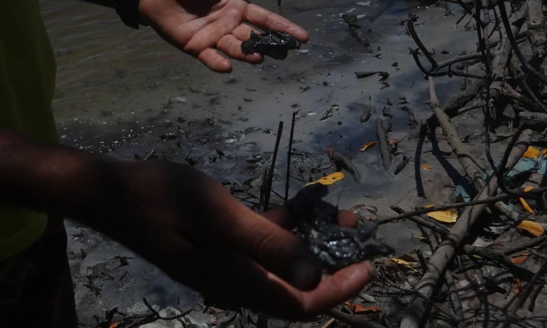 Pescador mostra o óleo que afetou o manguezal em Conde, na Bahia Foto: Janielson de Souza