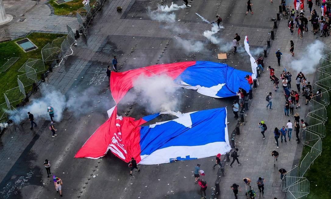 Manifestantes carregam uma bandeira do Chile rasgada. No fim da semana passada, o governo decretou estado de emergência e toque de recolher em várias cidades Foto: MARTIN BERNETTI / AFP