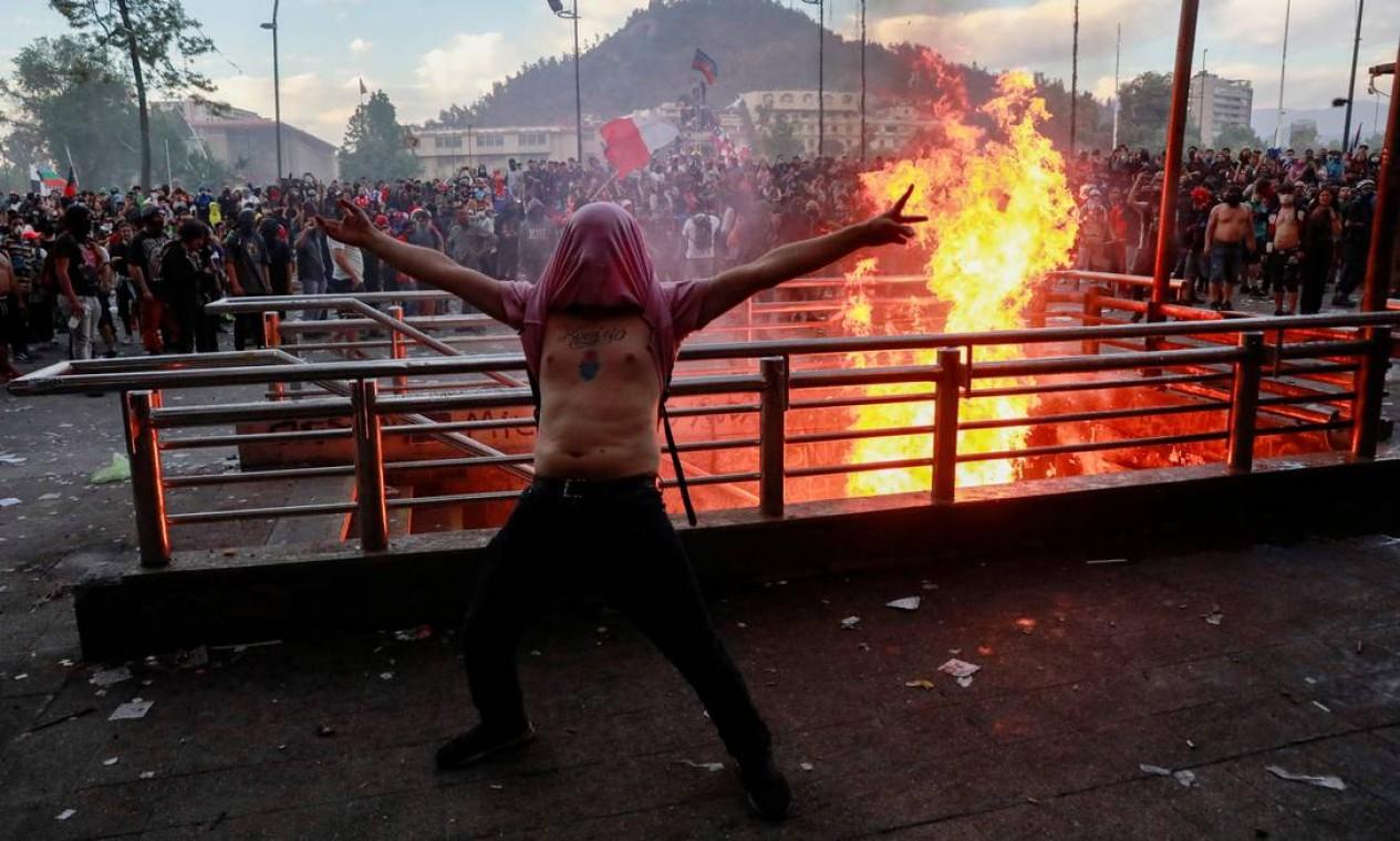 Manifestante diante de uma entrada do metrô: barreiras com fogo Foto: HENRY ROMERO / REUTERS