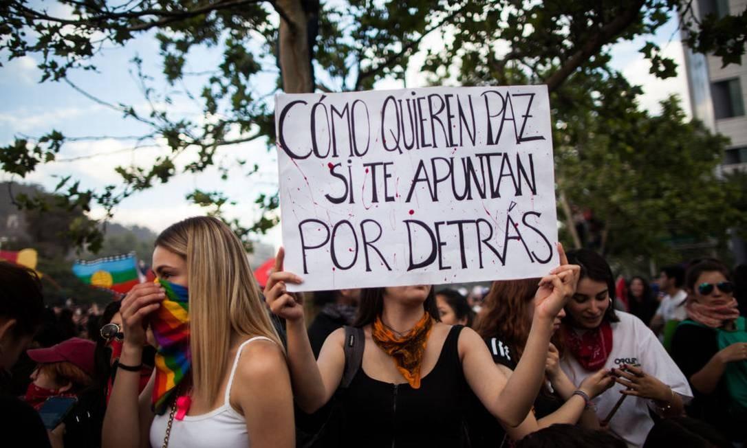 Cartaz com os dizeres 'Como querem paz se nos miram pelas costas', em protesto do dia 25 de outubro em Santiago Foto: NurPhoto / NurPhoto via Getty Images
