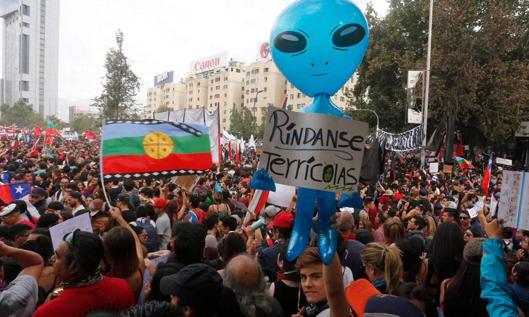 Cartaz com os dizeres 'Rendam-se terráqueos', em protesto do dia 25 de outubro em Santiago Foto: Marcelo Hernandez / Getty Images