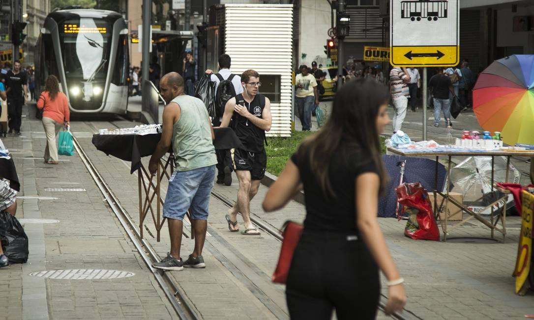 No Centro, ambulante retira banca para o VLT passar Foto: Guito Moreto / Agência O Globo