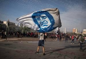 Manifestante carrega uma banndeira com a imagem de Víctor Jara, cantor e compositor chileno assasinado em 1973 pala ditadura de Augusto Pinochet Foto: PABLO SANHUEZA / REUTERS