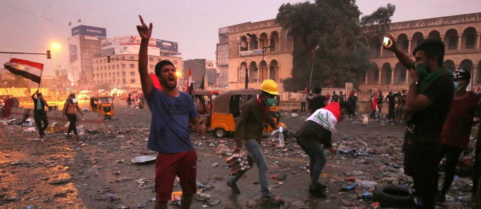 Manifestantes enfrentam a polícia perto da entrada da Zona Verde em Bagdá. Protestos se intensificaram em outubro, apesar da forte repressão das forças de segurança Foto: - / AFP