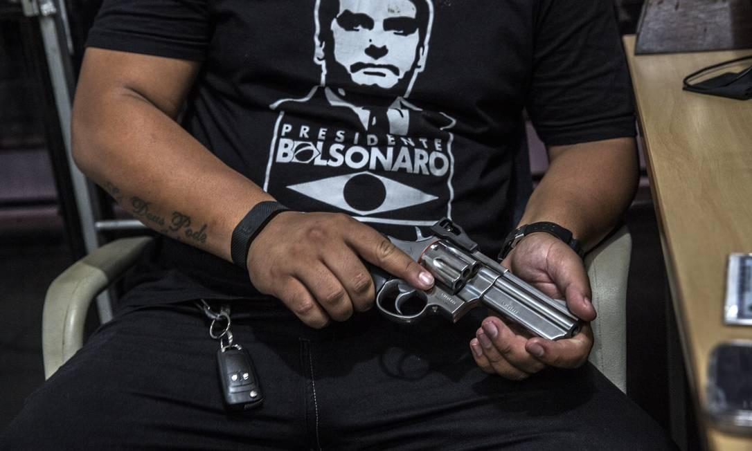 O comprador de armas exibe uma camiseta em apoio a Jair Bolsonaro em uma loja de armas em São João do Meriti, no Rio de Janeiro.  Os decretos que flexibilizam a regulamentação restritiva de armas foram as primeiras medidas do governo do presidente eleito Foto: Dado Galdieri / Agência O Globo