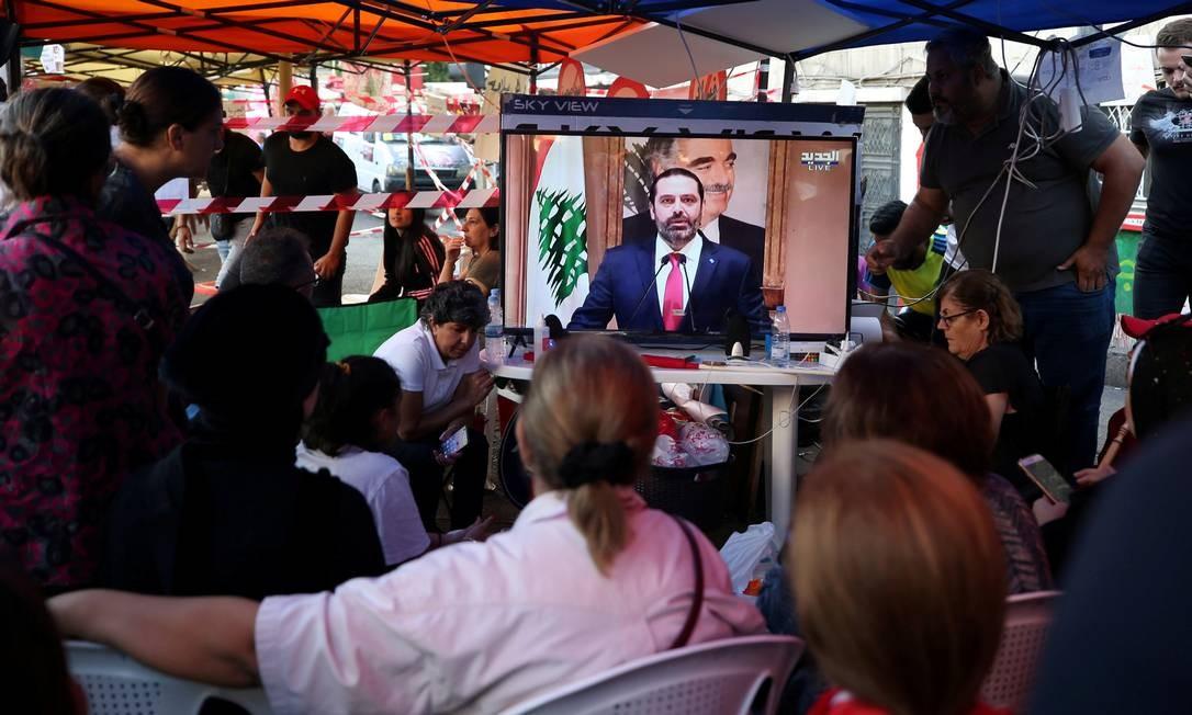 Manifestantes acampados no centro de Beirute ouvem discurso em que Hariri anunciou sua renúncia Foto: ALI HASHISHO / REUTERS