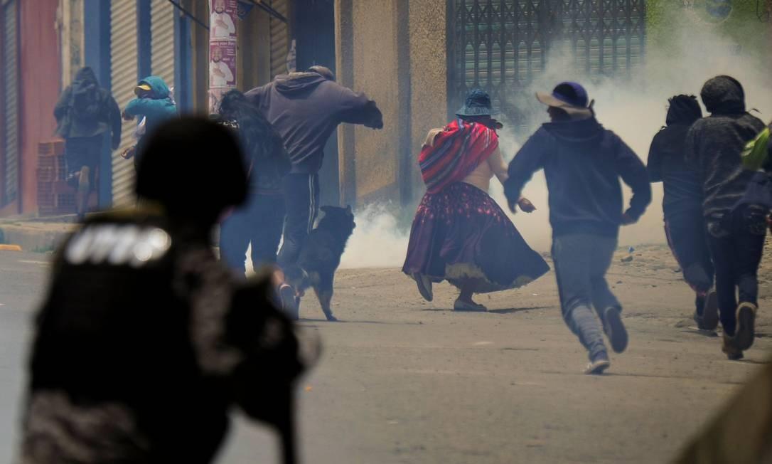 Pessoas que protestavam contra uma greve desencadeada pelo resultado das eleições de 20 de outubro fogem de gás lacrimogêneo em La Paz. Governo convidou, nesta terça-feira o candidato derrotado Carlos Mesa para participar de uma auditoria dos resultados eleitorais, cujos resultados provocaram protestos que já duram mais de uma semana Foto: JORGE BERNAL / AFP
