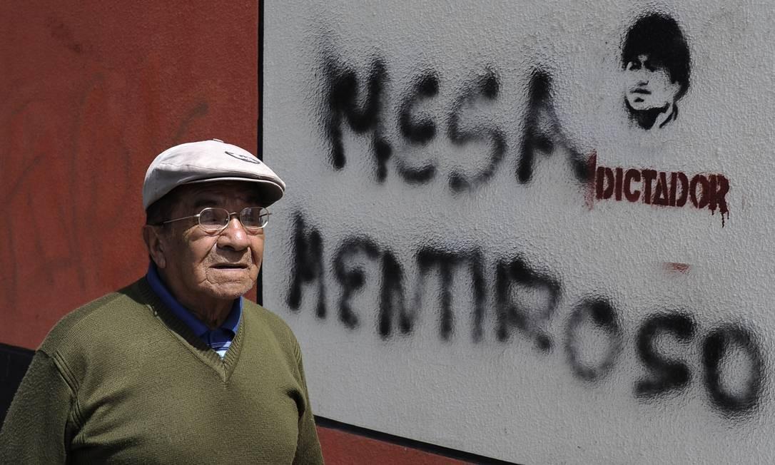 """Homem passa por uma pintura com a inscrição """"Mesa Mentiroso"""" e uma imagem do presidente Evo Morales sobre a palavra """"Ditador"""" Foto: JORGE BERNAL / AFP"""