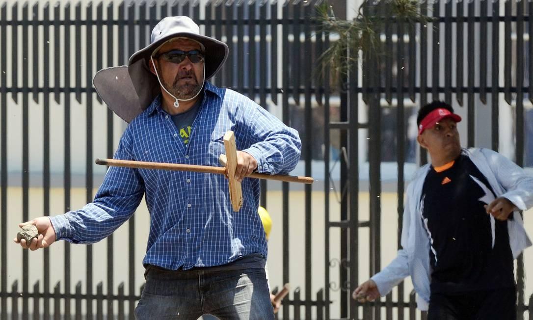 Partidários do candidato derrotado Carlos Mesa entram em confronto com os do presidente boliviano, Evo Morales, em Cochabamba. As suspeitas de fraude envolvem a chamada contagem rápida: uma apuração preliminar que na noite de domingo foi interrompida quando indicava um segundo turno e que ao ser retomada na segunda mostrava Morales vencendo no primeiro turno Foto: STR / AFP