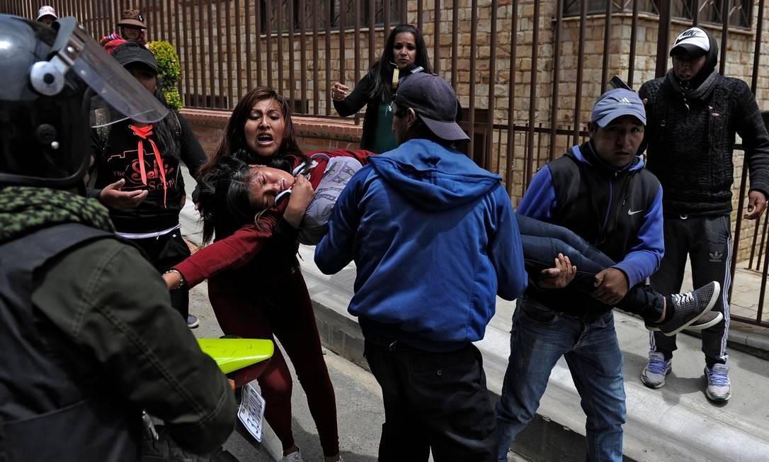 Manifestantes socorrem uma mulher que desmaiou devido ao gás lacrimogêneo durante um protesto contra uma greve desencadeada pelo resultado das eleições de 20 de outubro, em La Paz Foto: JORGE BERNAL / AFP