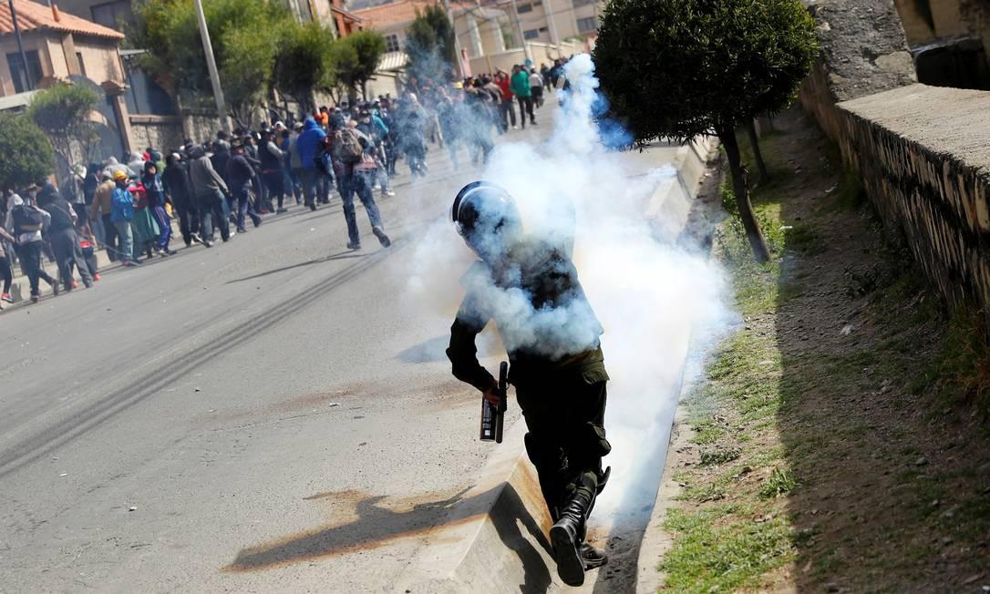 Um policial lança uma bomba de gás lacrimogêneo contra manifestantes durante protesto em La Paz Foto: Kai Pfaffenbach / REUTERS