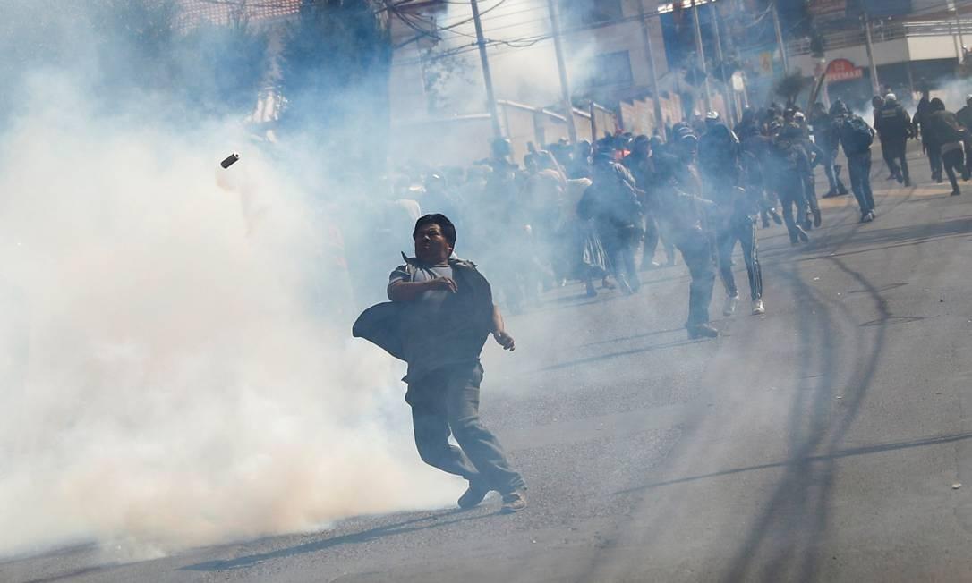 Manifestante joga de volta um cartucho de gás lacrimogêneo durante um protesto em La Paz Foto: KAI PFAFFENBACH / REUTERS