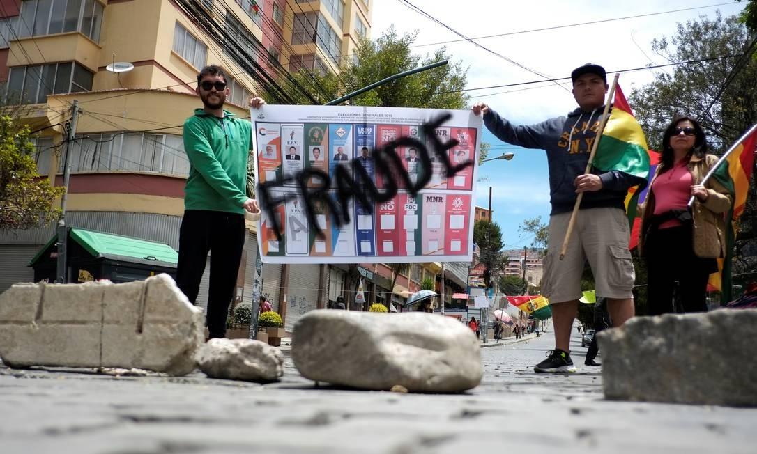 """Manifestantes seguram uma placa com a inscrição """"Fraude"""" em La Paz Foto: DAVID MERCADO / REUTERS"""