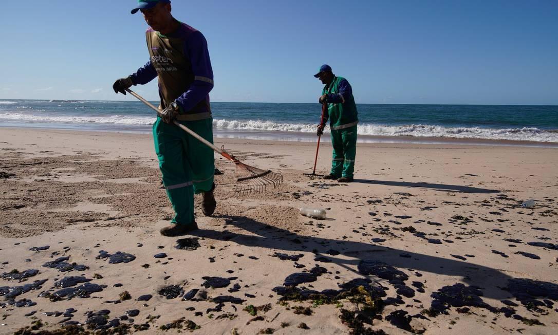 Agentes limpam óleo na Praia da Pituba, em Salvador Foto: Luca Castro/Fotoarena/Agência O Globo