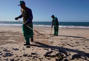 Agentes limpam óleo na Praia da Pituba, em Salvador Foto: Luca Castro / Fotoarena / Agência O Globo
