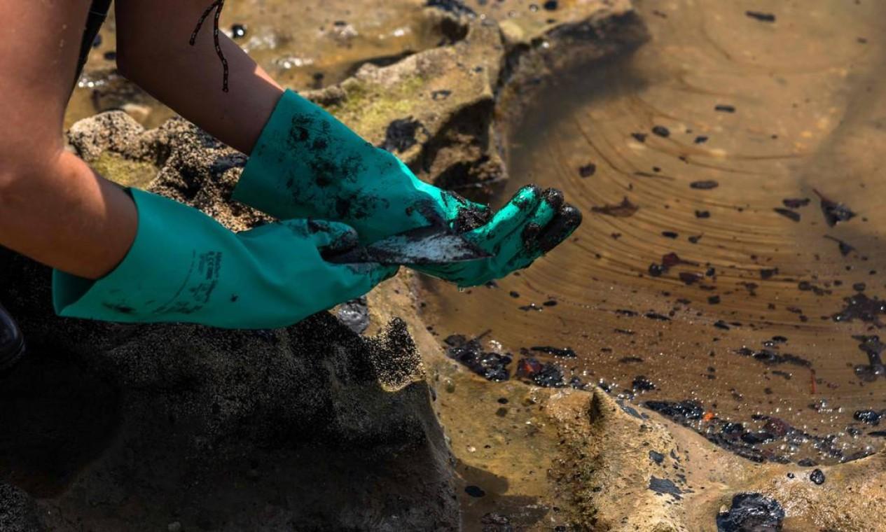 Voluntários se protegem com luvas de uso doméstico para retirar óleo derramado na praia de Pocas, na cidade de Conde, Bahia Foto: Mateus Morbeck / AFP - 27/10/2019