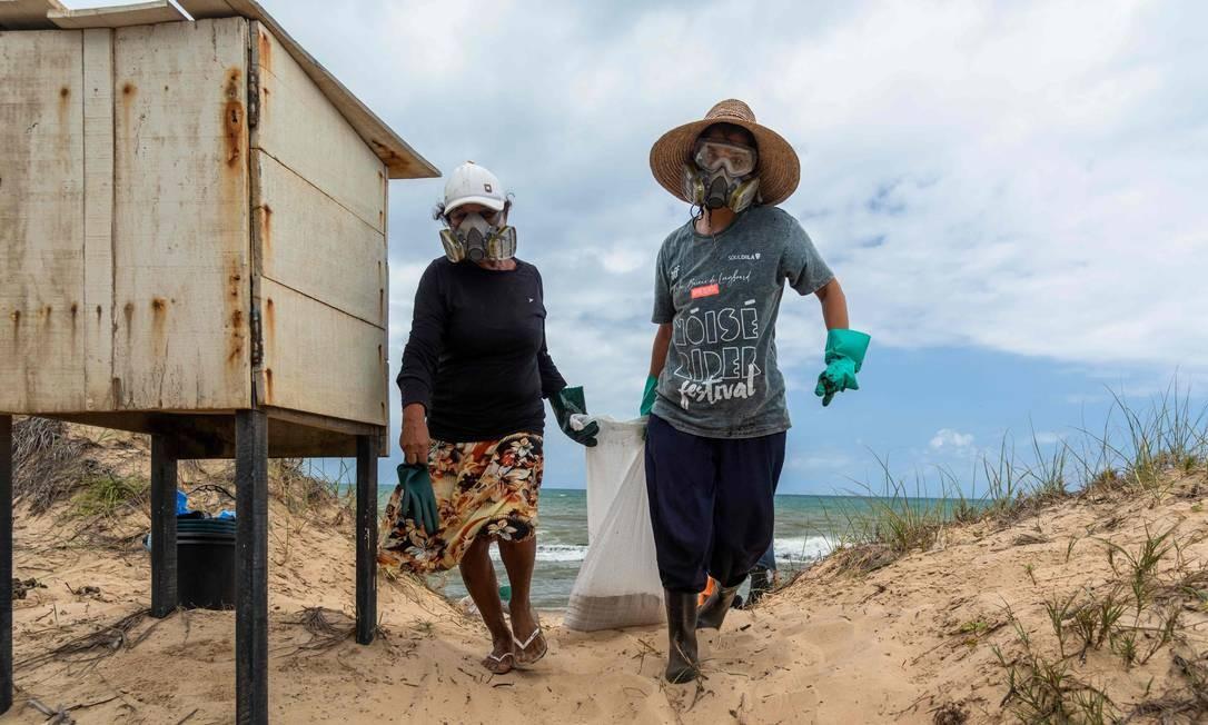 Voluntários carregam bolsa com óleo bruto derramado na praia de Pocas em Conde, Bahia Foto: Mateus Morbeck / AFP