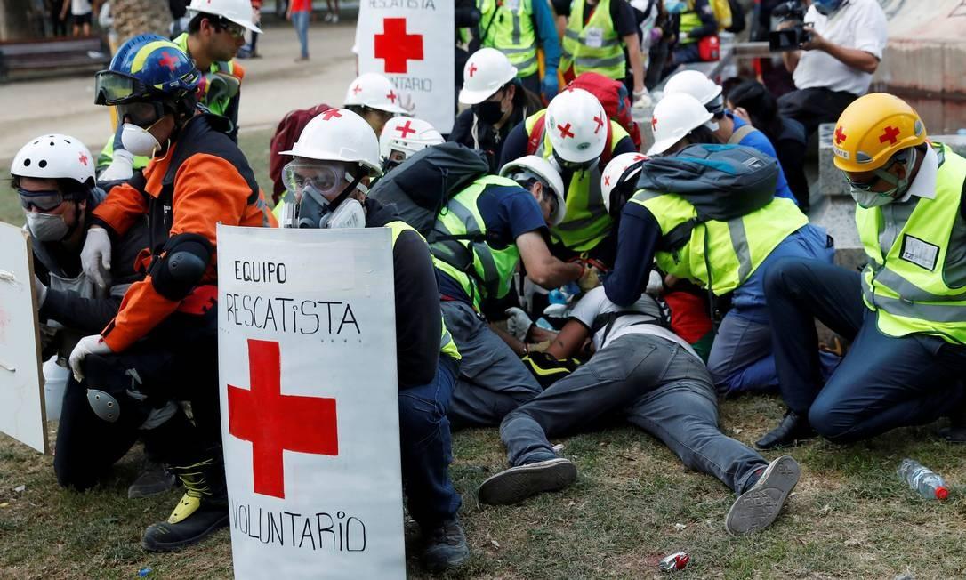 Manifestante ferido é atendido durante protesto em Santiago, Foto: JORGE SILVA / REUTERS