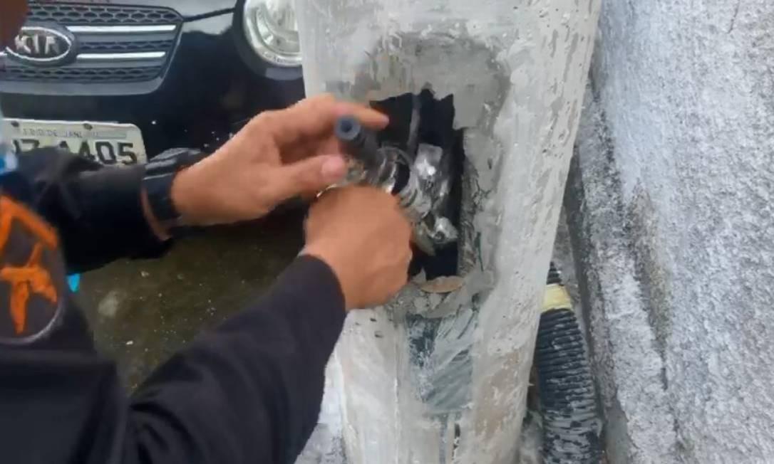 Um dos fuzis sendo retirado do poste Foto: Reprodução de vídeo / Polícia Militar