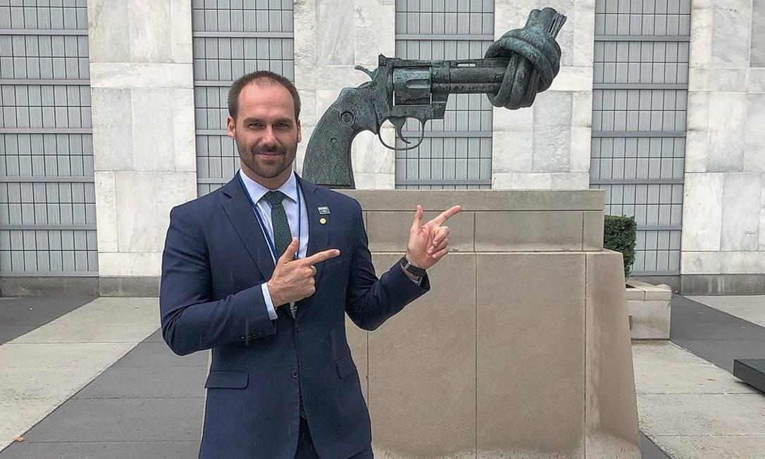 """Em foto postada em 26 de setembro de 2019, o deputado faz sinal de armas com os dedos diante de uma escultura contra violência, em frente ao prédio da ONU, em Nova York. """"As operações de paz da ONU acertadamente usam armas. Mas na entrada do prédio da ONU em NY fica essa escultura desarmamentista. Como todo bom desarmamentista eis a máxima 'armas para mim, desarmamento para os outros'"""", escreveu o deputado Foto:"""