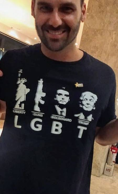 O deputado Eduardo Bolsonaro com uma camisa cuja estampa ironiza a sigla LGBT, utilizando as letras para exaltar os Estados Unidos, sua política de armamento, o presidente Jair Bolsonaro e o presidente americano, Donald Trump Foto: Reprodução