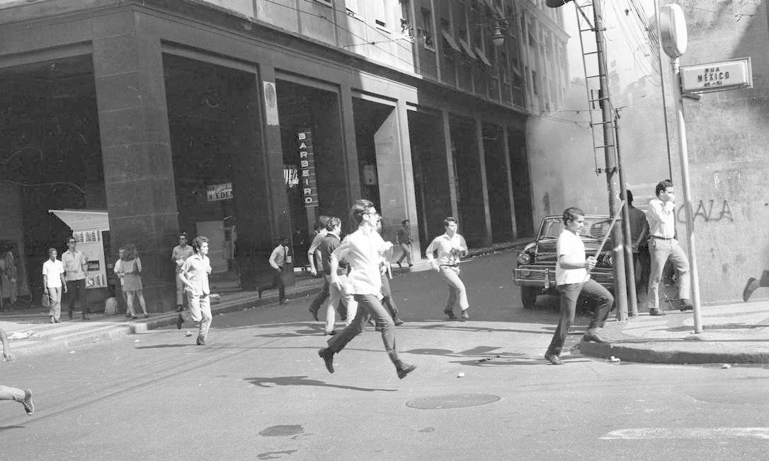 Pessoas correm em meio a fumaça das bombas de gás lacrimogêneo perto da Rua México Foto: Arquivo / Agência O Globo