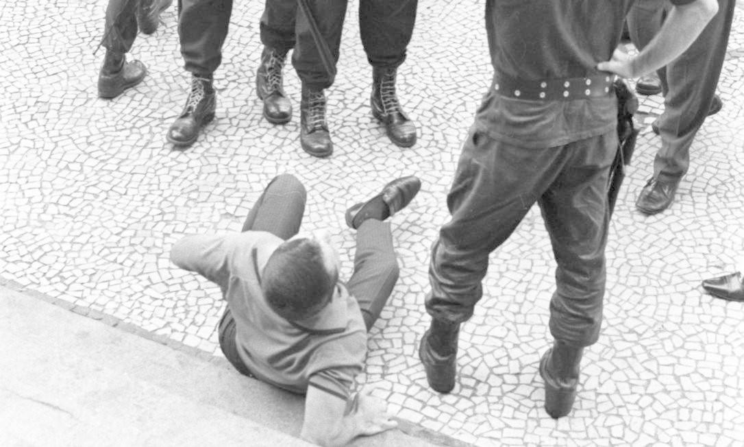 """Grupo de policiais próximo a um homem caído no chão durante a """"Sexta-feira sangrenta"""" Foto: Arquivo / Agência O Globo"""