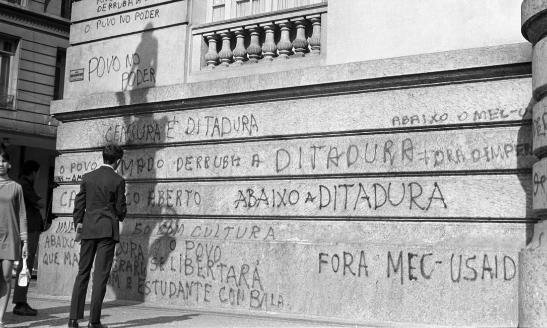 Na foto, homem lê a pichação de protesto na fachada do prédio, em maio de 1968 Foto: Arquivo / Agência O Globo