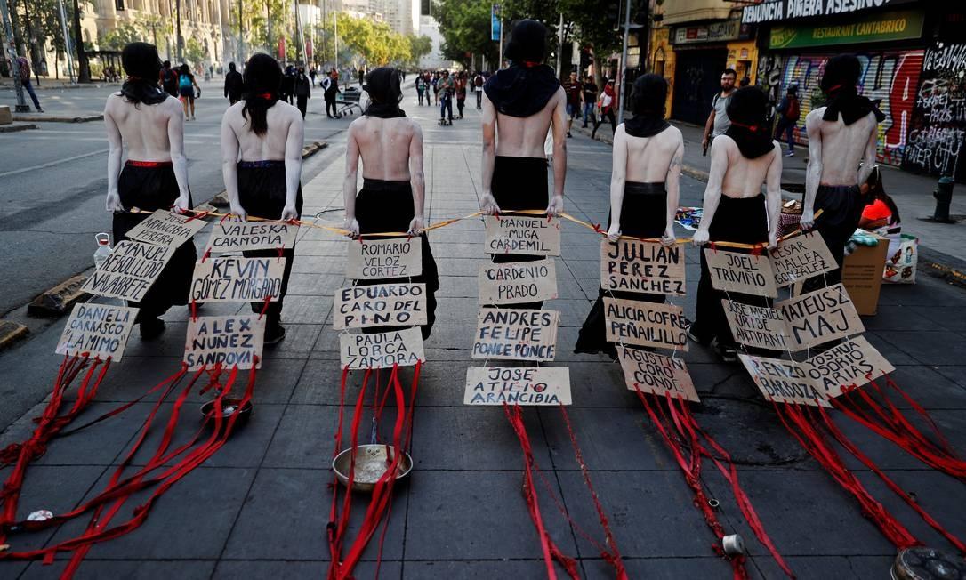 Manifestantes exibem os nomes daqueles que dizem serem vítimas dos protestos contra o governo chileno, iniciados há quase duas semanas Foto: JORGE SILVA / REUTERS