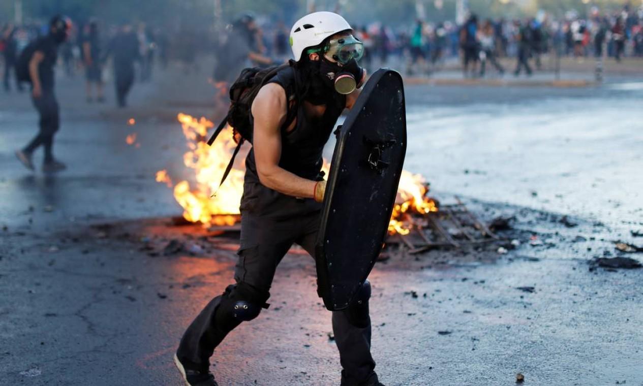 Um manifestante carrega um escudo durante um protesto contra o governo, em Santiago Foto: JORGE SILVA / REUTERS