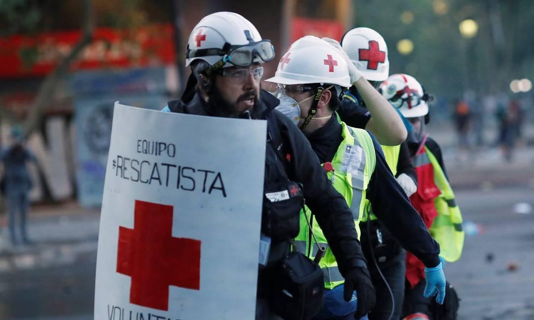 Médicos voluntários mantém um escudo para se protegerem durante um protesto em Santiago Foto: EDGARD GARRIDO / REUTERS