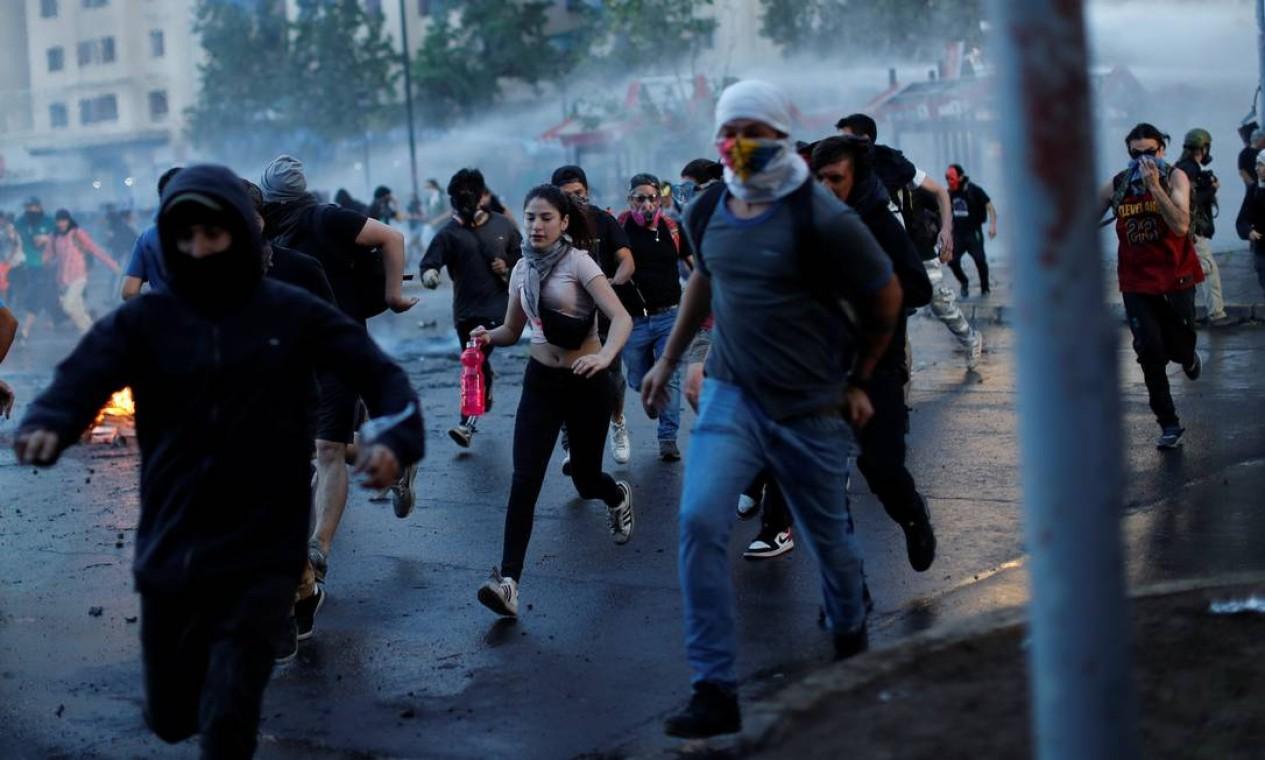 Manifestantes fogem da ofensiva policial, que utiliza canhões de gás lacrimogêneo e água para dipersar multidão Foto: JORGE SILVA / REUTERS