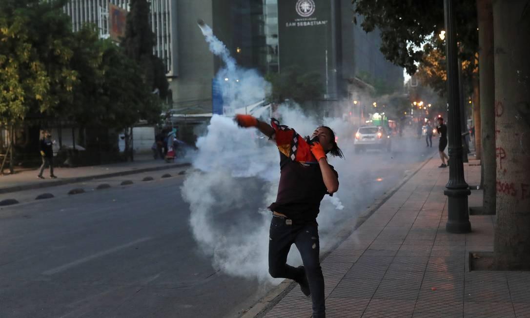 Manifestante joga bomba de gás lacrimogêneo durante um protesto contra o governo do Chile, em Santiago Foto: PABLO SANHUEZA / REUTERS