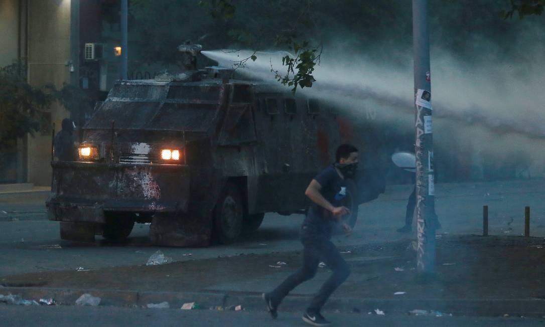 Manifestante foge de um canhão de água disparado pela polícia em Santiago Foto: EDGARD GARRIDO / REUTERS