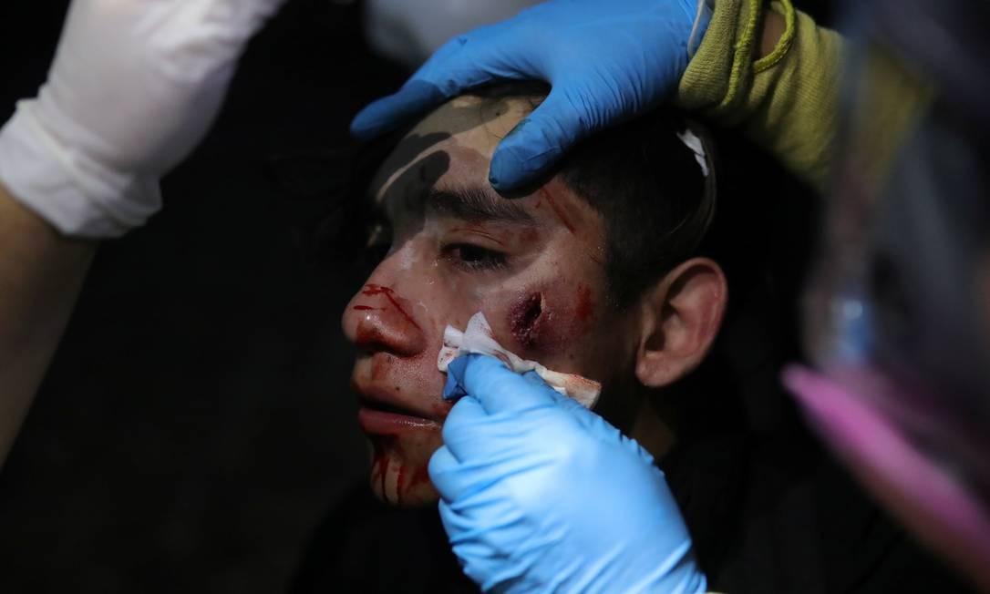 Uma manifestante recebe atendimento após ser ferida durante o protesto em Santiago Foto: PABLO SANHUEZA / REUTERS