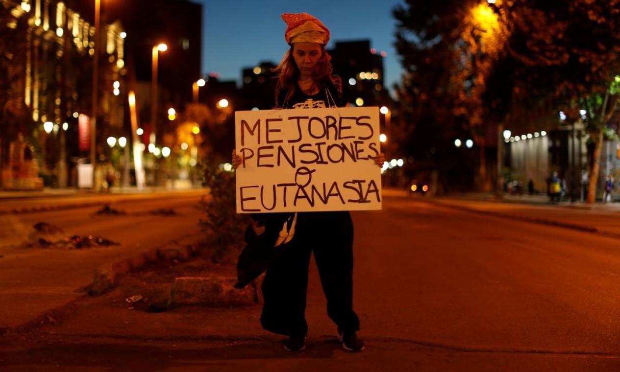 """Mulher exibe um cartaz com a inscrição """"Melhores pensões ou eutanásia"""" durante um protesto antigoverno, em Santiago, Chile Foto: JORGE SILVA / REUTERS"""