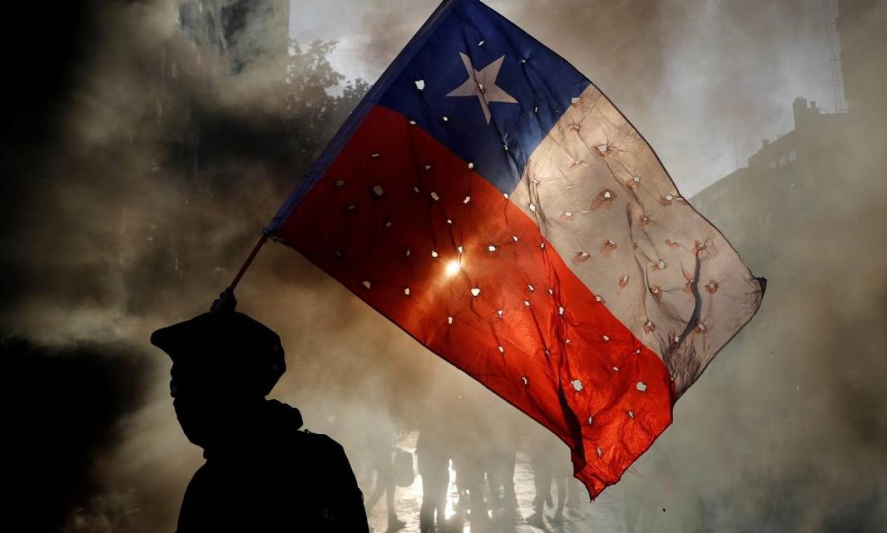 Manifestante agita uma bandeira do Chile cheia de buracos durante um protesto contra o governo, em Santiago Foto: HENRY ROMERO / REUTERS