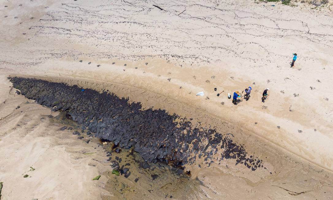 Imagem captada por drone mostra voluntários retirando óleo da praia das Poças, na cidade de Conde, na Bahia. Foto: MATEUS MORBECK / AFP
