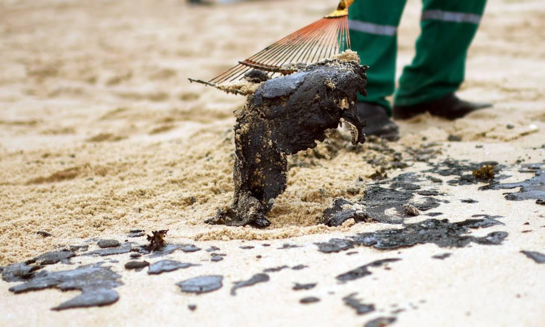 Funcionário remove resíduo de óleo na praia de Barra de Jacuipe, em Camaçari, Bahia Foto: Lucas Landau / Reuters