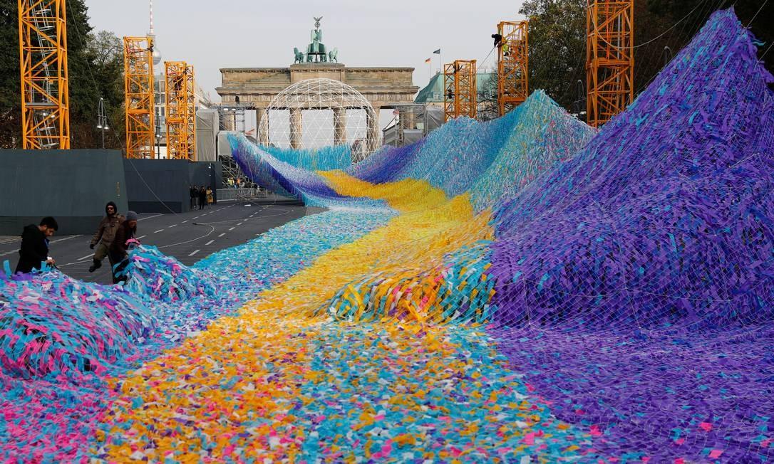 """Em Berlim, com o Portão de Brandemburgo ao fundo, trabalhadores fazem a preparação final para levantar a instalação artística """"Visões em Movimento"""", feita com 30 mil fitas com desejos escritos por 30 mil pessoas. Em 9 de novembro, a Alemanha festeja o 30º aniversário da queda do Muro de Berlim, fato que marcou o fim da Guerra Fria Foto: FABRIZIO BENSCH / REUTERS"""