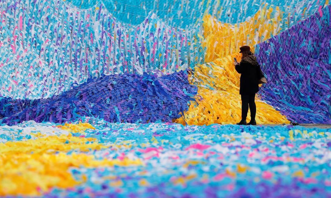 Uma mulher fotografa a instalação artística que carrega os desejos escritos em fitas de 30 mil pessoas, em Berlim Foto: FABRIZIO BENSCH / REUTERS